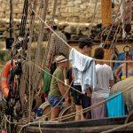 Junge Leute bereiten sich auf einem älteren Segelboot auf die Ausfahrt vor