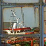 Fischtrawler verzerrt im Fenster eines Gebäudes gegenüber