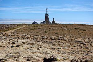 Wir sind unmittelbar an den Felsen zum Kap und blicken zurück auf das Sémaphore de la Pointe du Raz und Statue