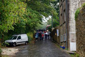 Japanische Touristen passieren im Regen das Château de Belon