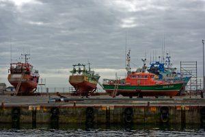 Im Hafen von Le Guilvinec auf dem Pier auf dem Gelände der Reparaturwerft aufgebockte Fischtrawler