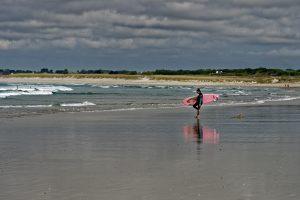 Surferin auf dem Weg ins Wasser hat sich vermutlich eine Muschel in den Fuß getreten