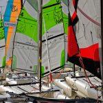 Die Segel der Katamarne am Strand flattern im Wind