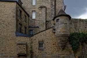 Gebäude mit mächtigem Mauerwerk stehen entlang des Flüsschens Le Steïr