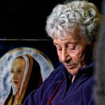 In der Crèperie 'Ty Coz' in Locronan eine ältere Dame am Tisch sitzend vor dem Bildnis einer jungen Frau