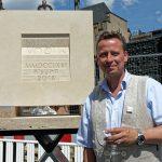 Steinmetzmeister Markus Heindl neben seinem Werk. Im Glas befindet sich kühles Wasser!
